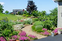 Replacements for the overgrown plant materials include a variety of mid-spring through summer-blooming perennials. Adjacent to the front walk these plants provide a distinctly English cottage garden effect.