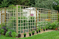 This wood frame garden enclosure is about fifteen feet wide, thirty feet long and eight feet high.